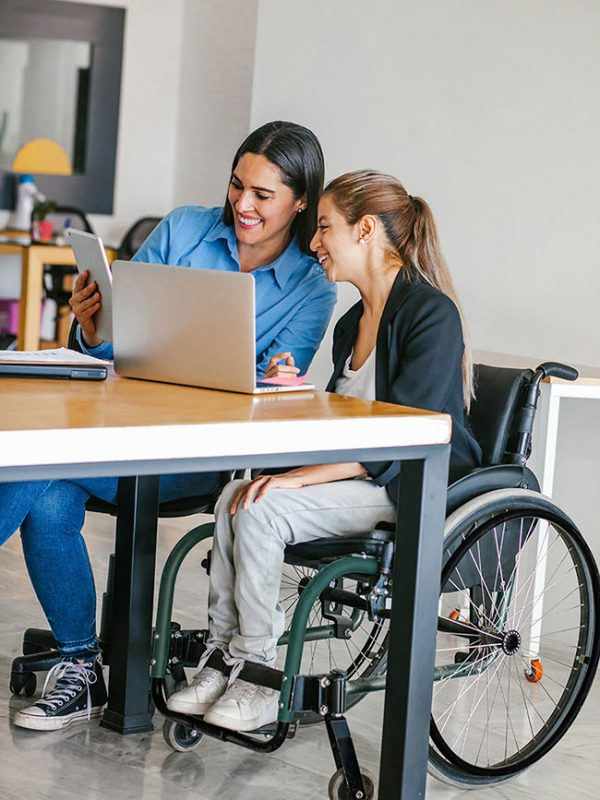 A doctor and a girl in a wheelchair looking at a computer